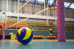 Yellow-blue volleyball on the floor in the gym. Team of athletes playing volleyball stock photography