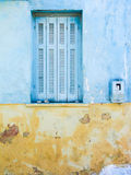 Yellow and blue wall with window. A ruined wall of a building in Greece with a window closed by light-blue shutters Stock Images