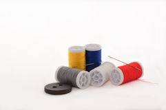 Yellow and blue, white thread spools on the white background Stock Images