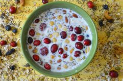 Yellow board with green bowl full of Oatmeal, chia seeds, fresh berries, seeds, nuts and milk. Making breakfast with some milk, oatmeal, nuts, seeds and berries royalty free stock photo