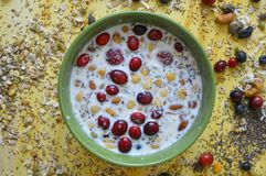 Yellow board with green bowl full of Oatmeal, chia seeds, fresh berries, seeds, nuts and milk. Making breakfast with some milk, oatmeal, nuts, seeds and berries stock photography