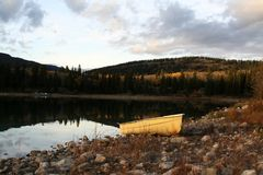 Yellow boat. On a rocky beach by a mountain lake Stock Image