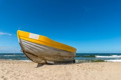 A yellow boat on the beach stock images