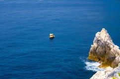 Yellow boat on blue dark water of Grotta di Lord Byron near coast with rock cliff, Portovenere town, Ligurian sea, Riviera di Leva. Nte, National park Cinque royalty free stock photos