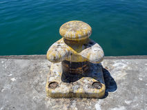 Yellow boat bollard covered in seagull droppings Royalty Free Stock Image