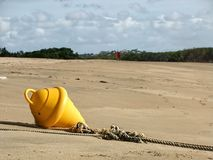Yellow boat buoy on sandy beach. Yellow buoy with anchorage ropes at low tide on a beautiful sandy beach Royalty Free Stock Photo