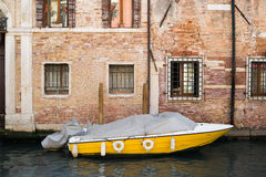 A yellow boat in the canals of Venice, Italy. A yellow boat in the canals of Venice Royalty Free Stock Photos