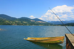 Yellow Boat near fishing road. Damaged yellow boat near a fishing road and the mountains in background Stock Photo