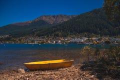 Yellow boat on shoreline of sea bay stock photography