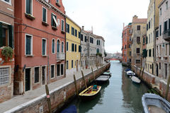 Yellow boat on small canal in Venice, Italy Stock Photos
