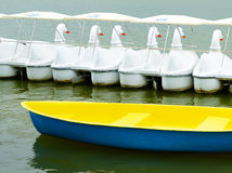 Yellow boat and Swan boats. On pond Royalty Free Stock Photo