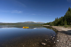 Yellow boat on tranquil lake with snow covered mountains Royalty Free Stock Photo