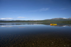 Yellow boat on tranquil lake with snow covered mountains Royalty Free Stock Photography