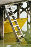 Yellow boat under the dock Stock Images