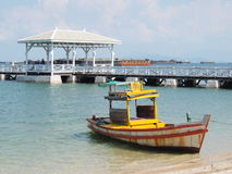 A yellow boat and white pier Stock Photography