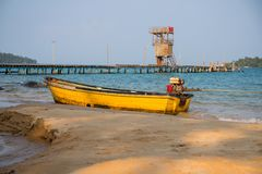 Yellow boat on white sand beach. Tropical island simple lifestyle. Rustic fishing boat. Wooden pier with small lighthouse. Idyllic paradise. Tropical island Royalty Free Stock Image