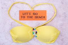 Yellow bodice leotard, text. Beach accessories on beige background. Let`s go to the beach Stock Photos