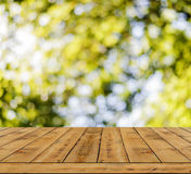 Yellow bokeh abstract light background, a lot forest bokeh with wooden floor Royalty Free Stock Photos