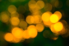 Yellow Bokeh balls abstract texture on green background. Colorfu. L. De focused background. Blurred bright light. Circular points royalty free stock photos