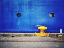 Yellow bollard and blue hull stock photo