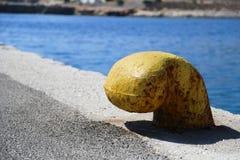Yellow bollard at harbor Stock Image
