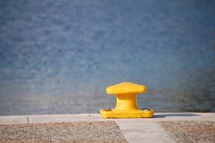 Yellow bollard on pier with sea view Stock Image