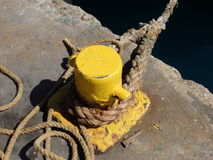 A yellow bollard in the windward islands. A sturdy ship's rope looped over a painted bollard in st. vincent and the grenadines stock photography