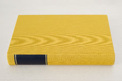 Yellow book with black frame on spine on the table Royalty Free Stock Images