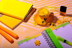 Yellow Books, Pens, Candles, Nail Polish. Top view of yellow coffee cup with a yellow daisy flower. Nail polish, candles, books, and felt flowers spread out on Royalty Free Stock Images