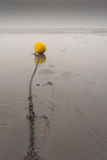 Yellow bouy on a chain on a beach Stock Photo