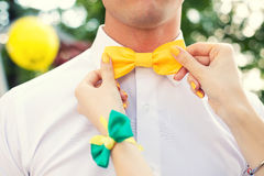 Yellow bow tie. Female hand man corrects a yellow bow tie Stock Image