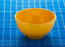 Yellow bowl on the blue pad Royalty Free Stock Image