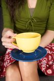Yellow bowl and blue plate over knees Royalty Free Stock Photo