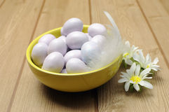 Yellow bowl of sugar candy mini Easter eggs, close-up. Stock Photo