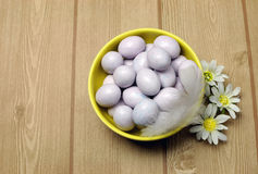 Yellow bowl of sugar candy mini Easter eggs with copy space. Yellow bowl of sugar candy mini Easter eggs on a natural timber table background royalty free stock photos