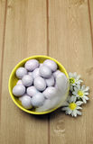 Yellow bowl of sugar candy mini Easter eggs, vertical with copy space. Yellow bowl of sugar candy mini Easter eggs on a natural timber table background stock images