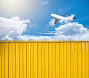 Yellow box container with airplane in sky. Yellow box container with airplane in blue sky Royalty Free Stock Photography