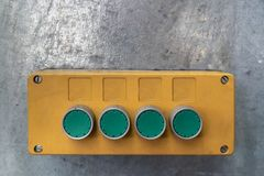 Yellow box with green push button, mounted on a galvanized steel carrier in a work hall royalty free stock image