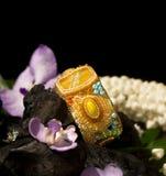 Yellow bracelet lies on coals Stock Image