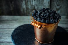 Yellow brass bucket with berry of blackberry stand on black stone stand on wood board. Top view. Yellow brass bucket with berry of blackberry stand on black stock photography