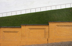 Yellow brick fence against the green grass slope and white wall Royalty Free Stock Image