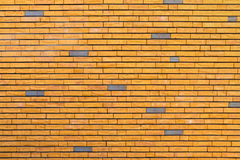 Yellow brick wall interspersed with some gray bricks Stock Image