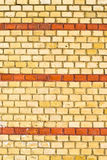 Yellow brickwall with red stripes Stock Photography