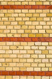Yellow brickwall with red stripes Royalty Free Stock Images