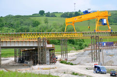 Yellow bridge crane on construction site of slovak D1 highway. Except for the crane there are some workers and cars. Royalty Free Stock Photography