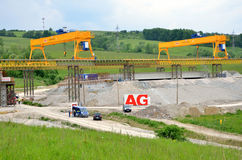 Yellow bridge crane on construction site of slovak D1 highway. Except for the crane there are some workers and cars. Stock Images