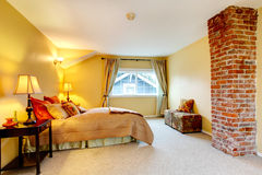 Yellow bright bedroom with brick colomn Stock Photos