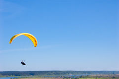 Yellow bright bright Paraglider in blue sky above the river and riverside. Bird`s eye panorama. Tom river. Tomsk city, Russia. Yellow Paraglider in blue sky Royalty Free Stock Photos