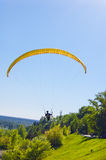 Yellow bright bright Paraglider in blue sky above the river and riverside. Bird`s eye panorama. Tom river. Tomsk city, Russia. Yellow Paraglider in blue sky Stock Photography