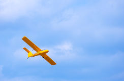 Yellow bright flying airplane in the blue sky Stock Photo